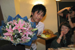 ケーキと花束を抱えて微笑むJINO@上海氏:クリックで拡大